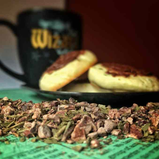 In the background a slightly blurred black mug with writing. Forward of that, a plate of cookies with chocolate icing, in front of that an artistic screwing of cacao nib bits and peppermint.