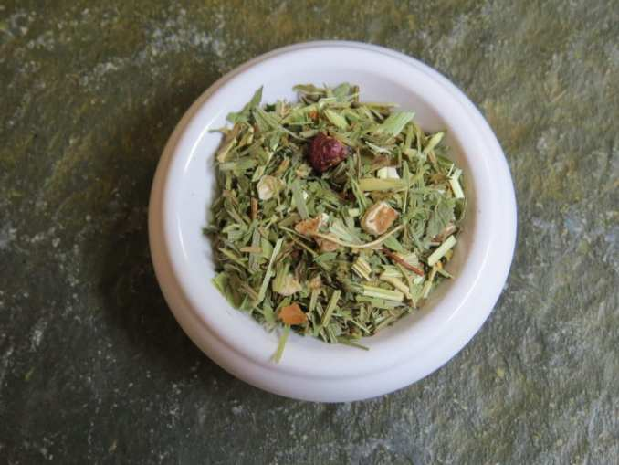 A small white bowl filled with a blend of horsetail, dandelion root, hawthorn berries, oatstraw, alfalfa, and peppermint. It is a close-in shot, though you can still see a bit of the green textured stone table in the background.