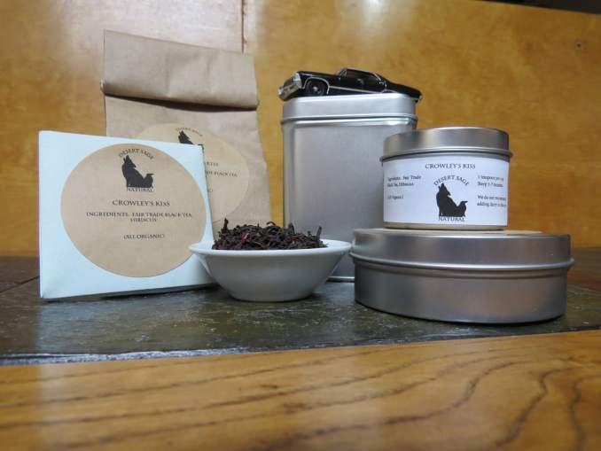 "A small white bowl full of a blend of hibiscus flowers and black tea. It is surrounded by an array of tea tins, a small origami packet of a size to hold a single teabag, and a bag of tea. The Supernatural Impala is perched atop the largest tin. The labels read: ""Crowley's Kiss, Ingredients: Fair Trade Black Tea, Hibiscus Flowers, (All Organic)"""