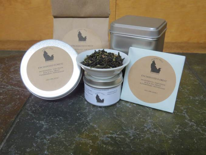 """A small white bowl, perched on top of a tea sample tin, filled with a blend of black tea, peppermint, and elderberries. Arrayed around it are a larger sample tin, a bag, a tea tin, and an origami packet of a size to hold a teabag. The labels read: """"Enchanted Forest, Organic Ingredients: Fair Trade Black Tea, Dried Elderberries, Peppermint, (All Organic)"""" The table they sit on is a textured green stone. The background is a light woodgrain."""