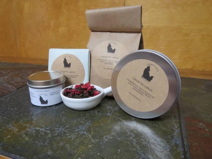 """A small white bowl shaped a bit like a pan filled with green tea and bits of freeze dried raspberries, circled by 2 tea tins, an origami packet with a teabag inside, and a bag of tea. The labels read """"Galactic Green, Organic Ingredients: High Mountain Green Tea, Freeze-dried Raspberries, (All Organic)"""