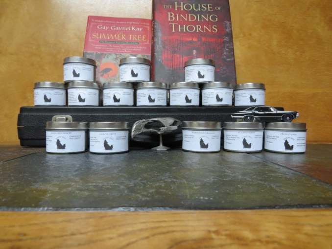 An array of tea tins, on and around a flute case. A Bird of Prey and the Winchester's car pose with the teas. Behind the top row are two books.