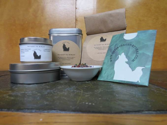 """A small white bowl full of a blend of freeze-dried raspberries, lemon balm, and lavender. Around the bowl is an array of tea tins, a bag of tea, and a cardboard slipcover holding a single teabag. The labels read: """"No Sleep 'Til 'Burque, Ingredients: Freeze-Dried Raspberries, Lavender, Lemon Balm, (All Organic)"""""""