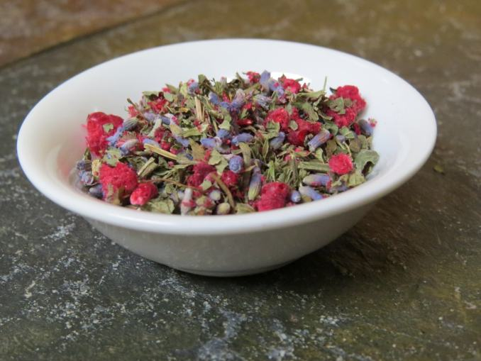 A small white bowl on a green textured stone table. The bowl is filled with a blend of lavender, lemon balm, and freeze dried raspberries.
