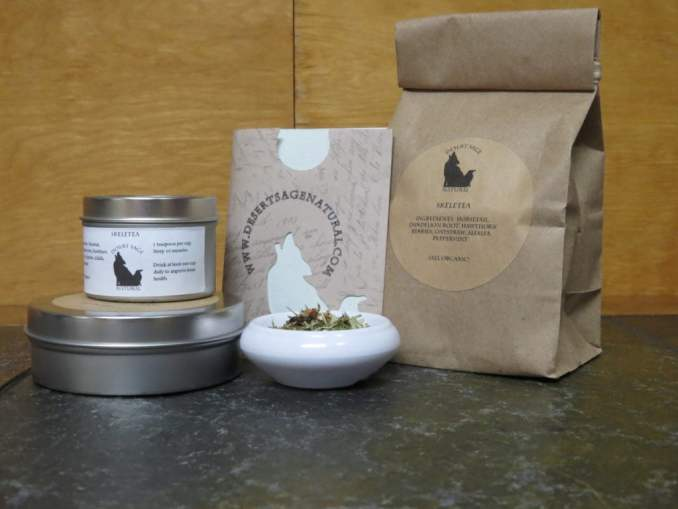 """A small white bowl fill of a blend of green herbs and hawthorn berries, to the side of it are two stacked tea tins, behind it is a paper packet with the Desert Sage Natural logo and website that looks like it would hold a teabag, and a bag filled with tea. The labels read: 'SkeleTea, Ingredients: Horsetail, Dandelion Root, Hawthorn Berries, Oatstraw, Alfalfa, Peppermint (All Organic)"""""""