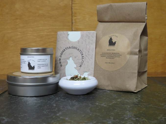 A small white bowl fill of a blend of green herbs and hawthorn berries, to the side of it are two stacked tea tins, behind it is a paper packet with the Desert Sage Natural logo and website that looks like it would hold a teabag, and a bag filled with tea. The labels read: 'SkeleTea, Ingredients: Horsetail, Dandelion Root, Hawthorn Berries, Oatstraw, Alfalfa, Peppermint (All Organic)""
