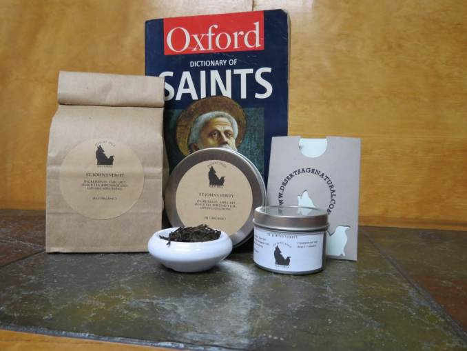"A small white bowl filled with a blend of black teas surrounded by an array of tea tins, bags, and a teabag holder with the Desert Sage Natural logo and website on it. Behind the array is a blue and red copy of the Oxford Dictionary of Saints. The labels read: ""St. John's Verity, Earl Grey Tea (Bergamot Oil, Black Tea), Lapsang Souchong, (All Organic)"""