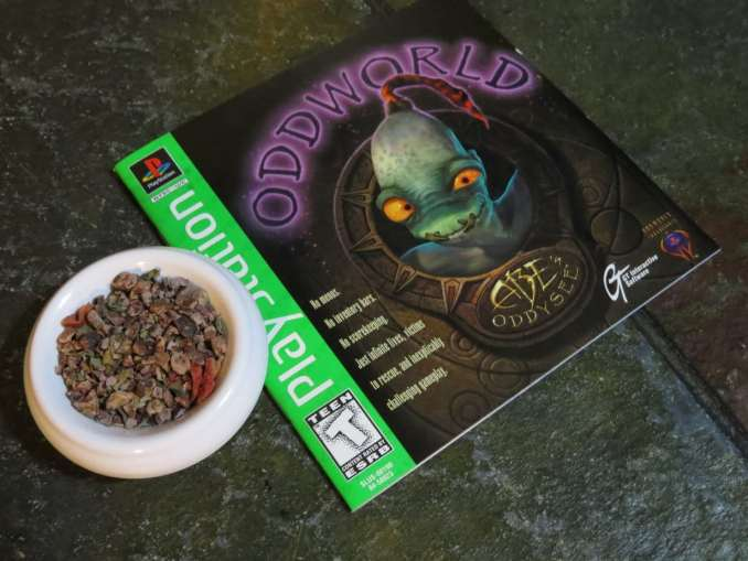 """The shot is taken from above a small white bowl and the leaflet for the game """"Oddworld."""" The bowl is full of a blend of cacao nibs, freeze dried strawberries, and basil. The stone underneath is green and textured."""
