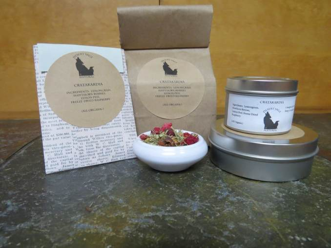 A small white bowl full of a blend of freezedried raspberries, lemon peel, lemongrass, and hawthorn berries. It is surrounded by a tins and bags of tea, and a small paper packet that could hold a single teabag.