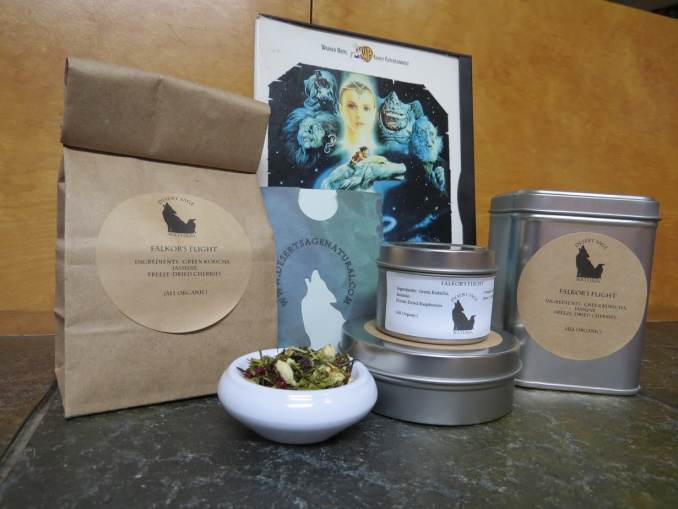 A small white bowl full of a blend of green kukicha, cherries, and jasmine is surrounded by an array of different tea tins, a bag full of tea, a small paper packet with the Desert Sage Natural logo cut out of it that looks like it could hold a teabag, with the case for the Neverending Story behind the array.