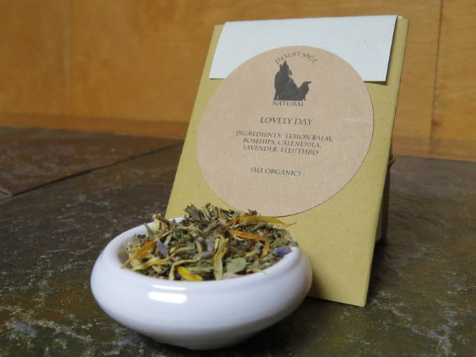 "A small white bowl with a blend of lemon balm, rosehips, calendula, lavender, and eleuthro. It is set on a green textured stone table. Behind it is a rectangular packet. The label on the packet reads: ""Lovely Day, Ingredients: Lemon Balm, Rosehips, Calendula, Lavender, Eleuthro, (All Organic)"""