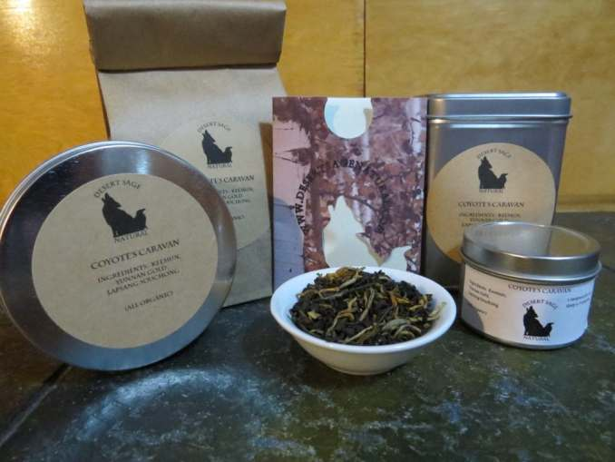 """A small white bowl filled with a blend of black teas. It is surrounded by an array of tea tins and a bag of teas. The labels state """"Coyote's Caravan, Ingredients: Keemun Black, Yunnan Gold, Lapsang Souchong All Organic."""""""