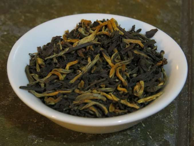 A small white bowl filled with a blend of black and golden teas.