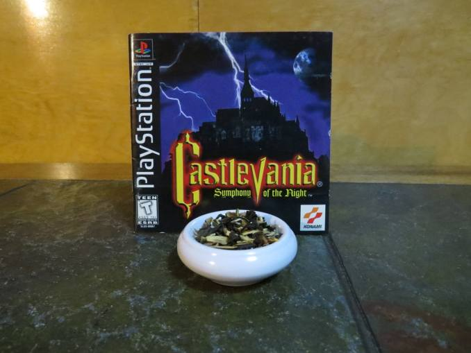 A small white bowl full of a blend of Lapsang, Licorice, and lime. It is set on a textured green stone table, with the leaflet from Castlevania's Symphony of the NIght propped up behind.