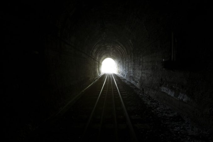 A tunnel with train tracks in it, dark, lit slightly from the far end, where you can see the arch of the exit.