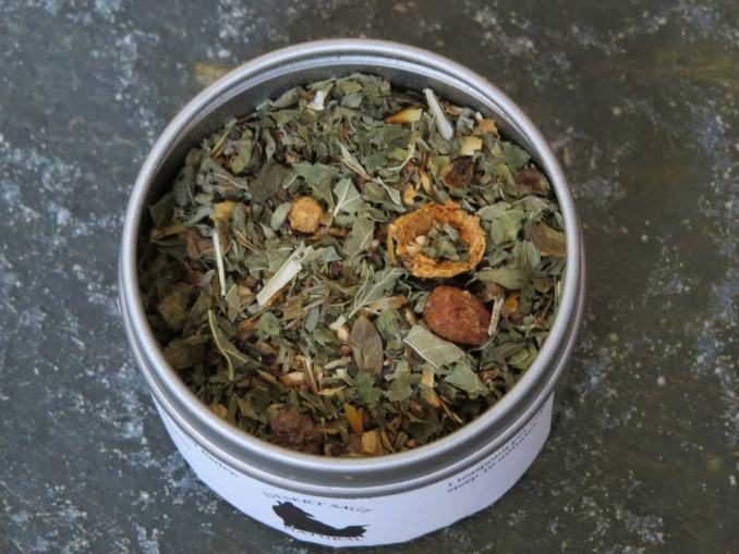 A small circular metal tin, filled with a blend of Lemon Balm, Hawthorn Berries, and Malted Barley.  The shot is from above the tin, so you can clearly see the herbs, as well as the textured green marble table beneath the tea.