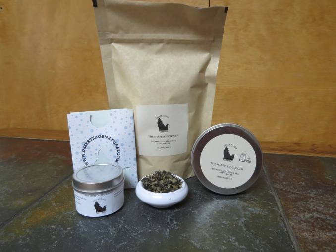 """A small white bowl of tea filled with a blend of lemon balm and black tea.  To either side are tea tins, behind it a large bag and a small rectangular packet that looks as if it could hold a teabag.  The labels read: """"The Shapes of Clouds, Ingredients:  Black Tea, Lemon Balm, (All Organic)."""