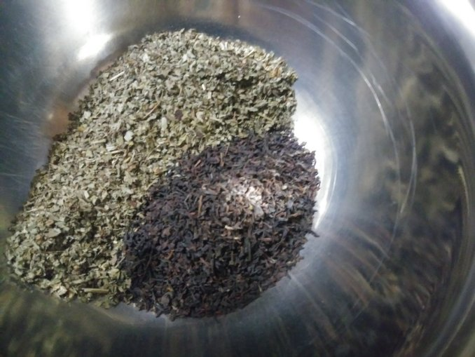 Closeup image of the inside of a metal bowl, you can only see hints of one edge - with lemon balm and black tea piled in a bowl next to each other.  The herbs reflect in the side of the bowl, too.