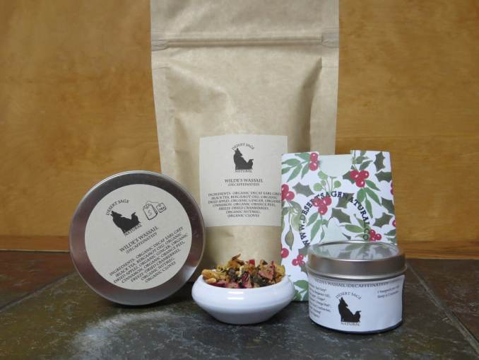 """A small white bowl on a textured stone table, the background behind being a mid-range small grained wood.  Behind the bowl is a bag, to the left is a circular tin up on edge, to the right is a rectangular packet with the Desert Sage Natural logo of a size to hold a teabag and a smaller circular tin.  The labels read """" Wilde's Wassail (Decaffeinated), Ingredients:  Earl Grey, Dried Apple, Ginger, Cinnamon, Orange Peel, Freeze-Dried Cranberries, Nutmeg, Cloves""""  It also indicates that everything except the Cranberries are organic."""