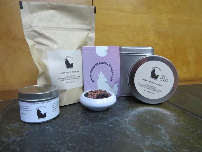 """A bag of tea, two circular tea tins, a taller square tin, and a teabag packet arrayed around a small white bowl full of a combination of cacao nibs and blueberries.  The labels read """"First Taste of Home"""" and list those two ingredients, as well as stating that they are both organic."""
