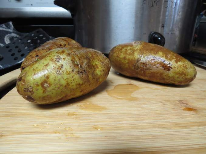 3 potatos, still slightly damp, on a cutting board.  The image is zoomed in fairly close on them, but there is a slow cooker in the background, the settings written around the dial in sharpie pen.