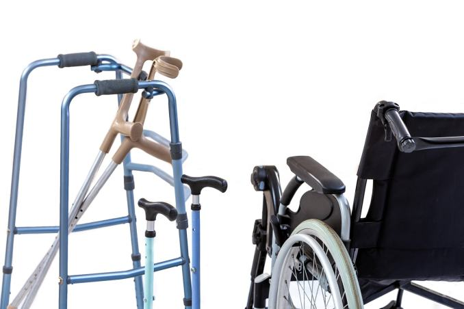 Forearms crutches leaning against a walker, two single handed canes in between that and a wheelchair.