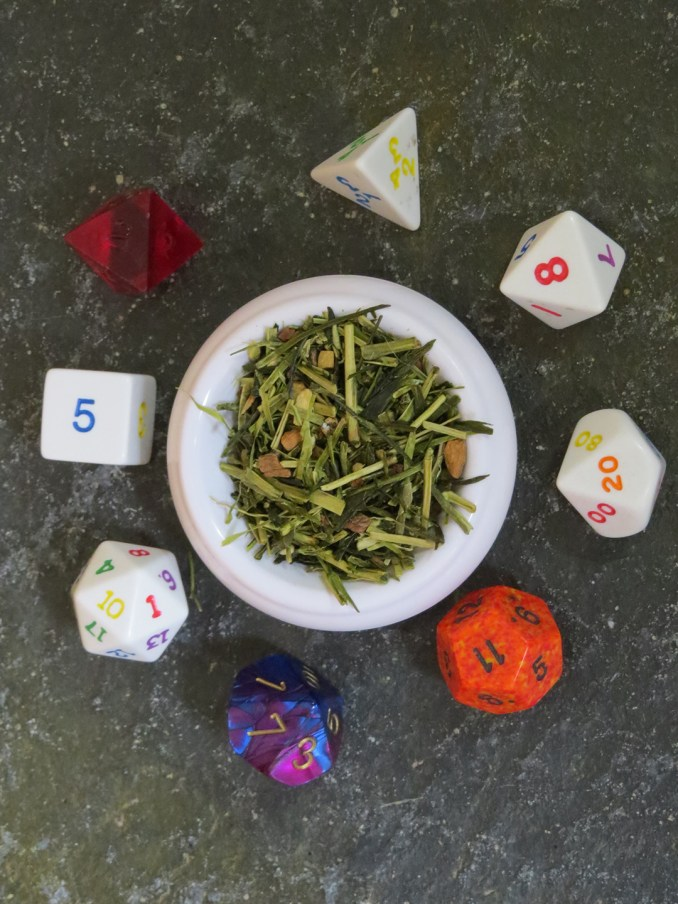 A small white bowl full of a blend of green tea and chai spices, set on a green textured stone table, with an array of dice around it.