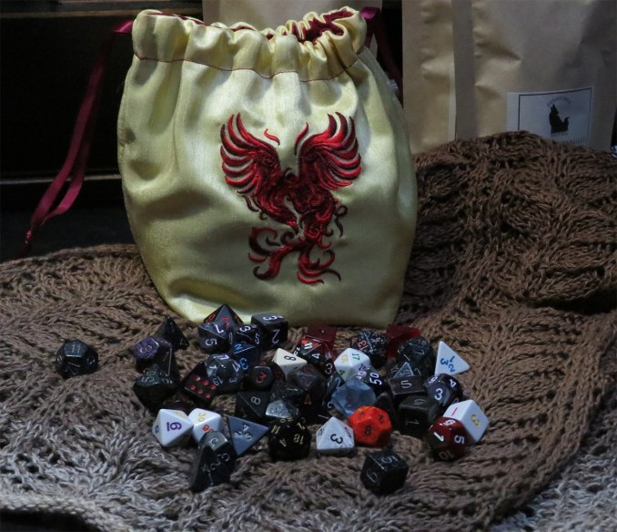 A pale yellow dice bag with a phoenix embroidered on it in reds.  It sits on a glorious shawl in browns, beaded.  Scattered atop the shawl in front of the bag is an array of dice.