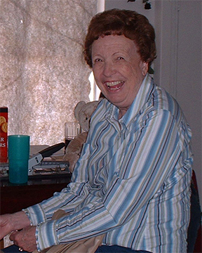 An older woman in a striped dress shirt, sitting at a table, wide smile, caught mid-laughter.