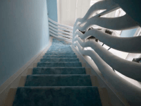 Curvilinear Staircase designed by Danielle Moudaber covered with light blue carpet (photo by Gisela Torres)