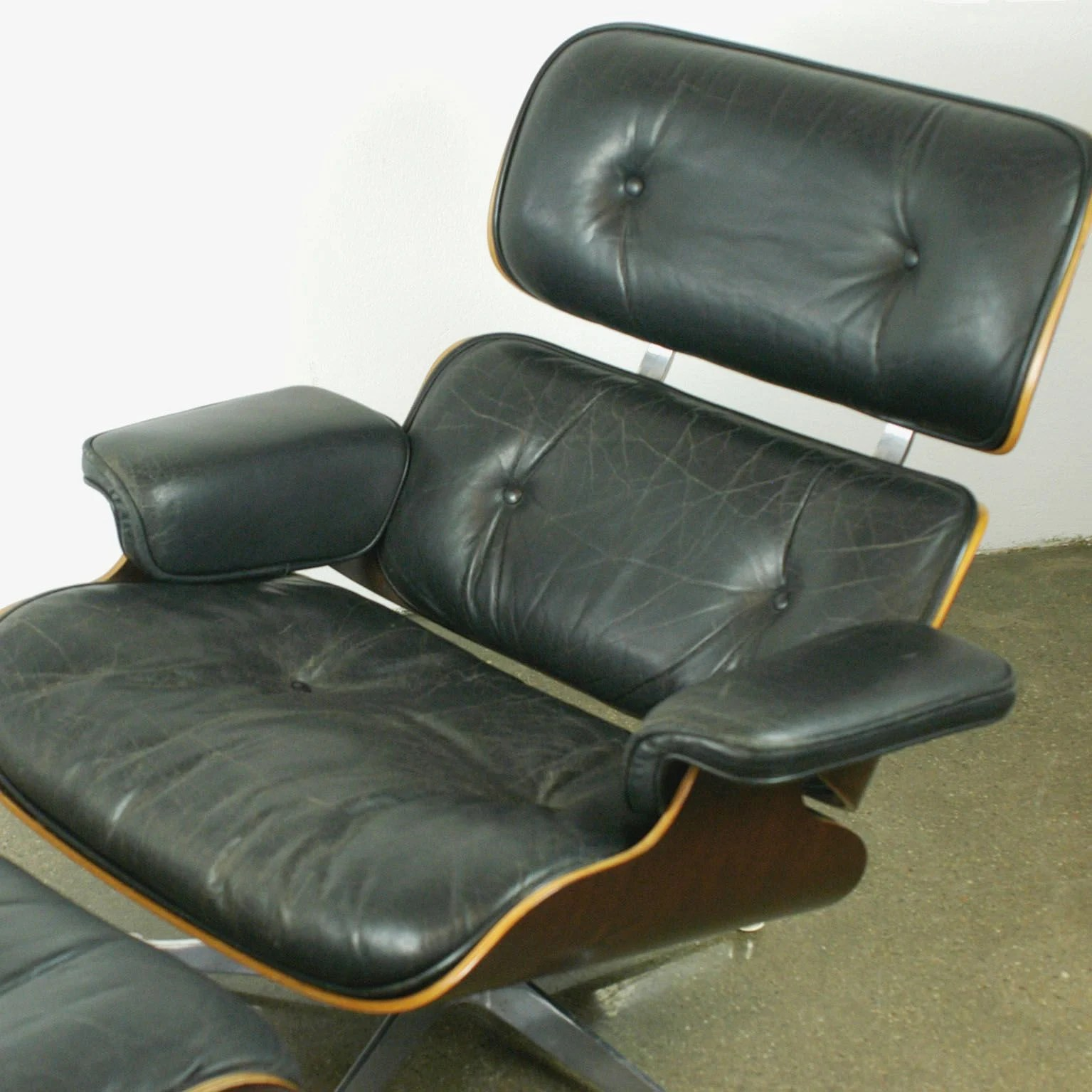Vintage lounge chair and ottoman in rosewood by Eames for