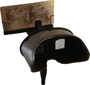 The more economical handheld Holmes Stereoscope viewer has a wooden stand and handle. Mine is made with a decorative metal hood. Many are made completely of wood. Two prismatic lenses angle your vision. The card can be adjusted closer or more distant to get the right focal point for each card.