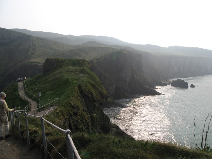 Carrick-a-Rede Island and the sheer cliffs around Carrick-a-Rede Rope Bridge. There are large caves in the cliff and the island.