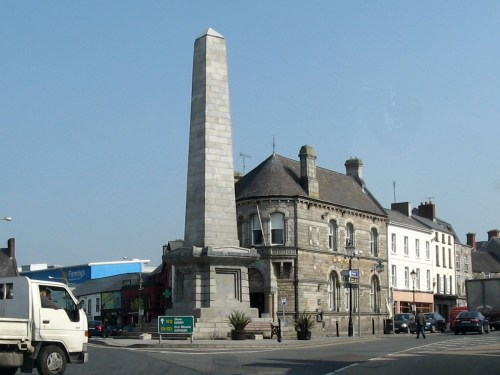 Dawson Obelisk, Church Square, Monaghan, Ireland commemorate Colonel Dawson, lost in the Crimean War. Ruskinian-Gothic Bank of Ireland building with curved front.