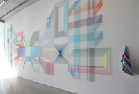 adrian esparza weaves and nails serape threads to the wall