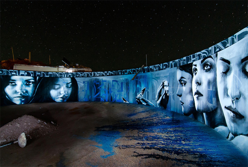 artists paint circular mural inside an abandoned water tank in the desert