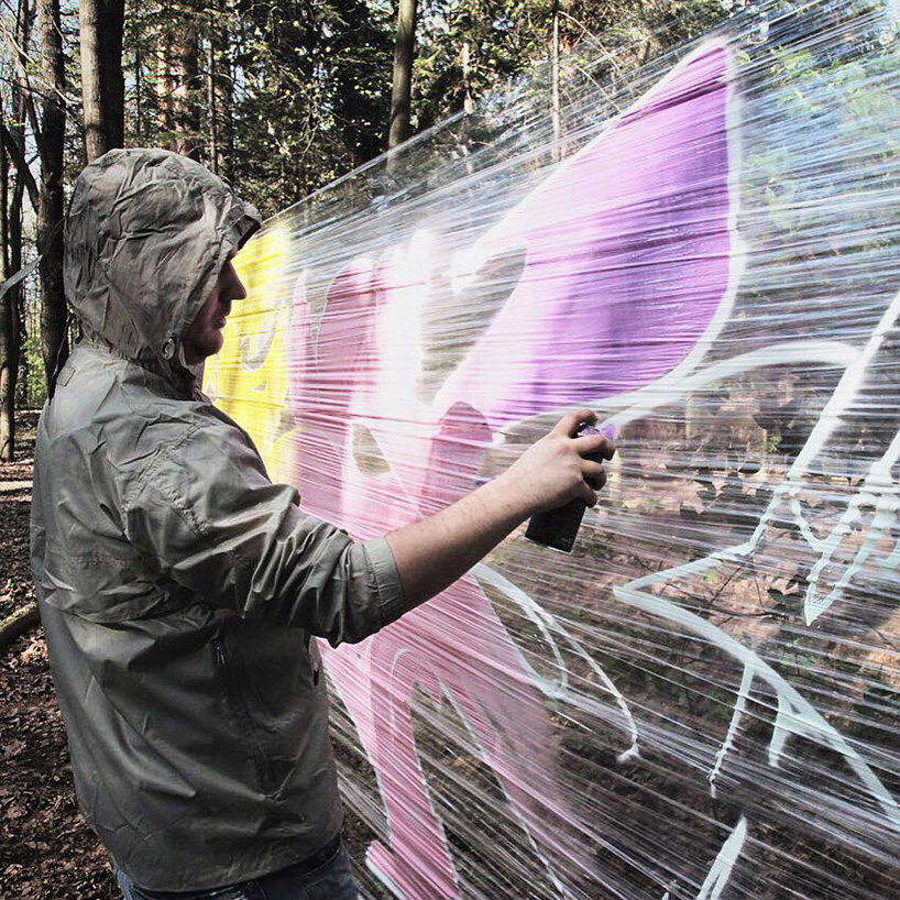 artist paints oversized animals on plastic wrap in the middle of the forest