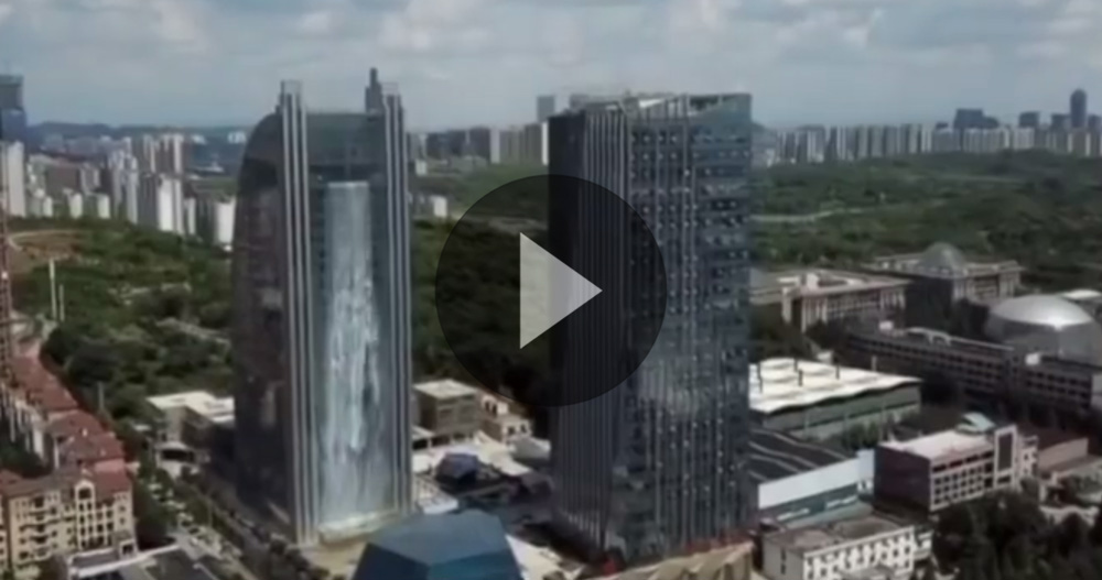 watch 100 meter waterfall cascades off a skyscraper in china