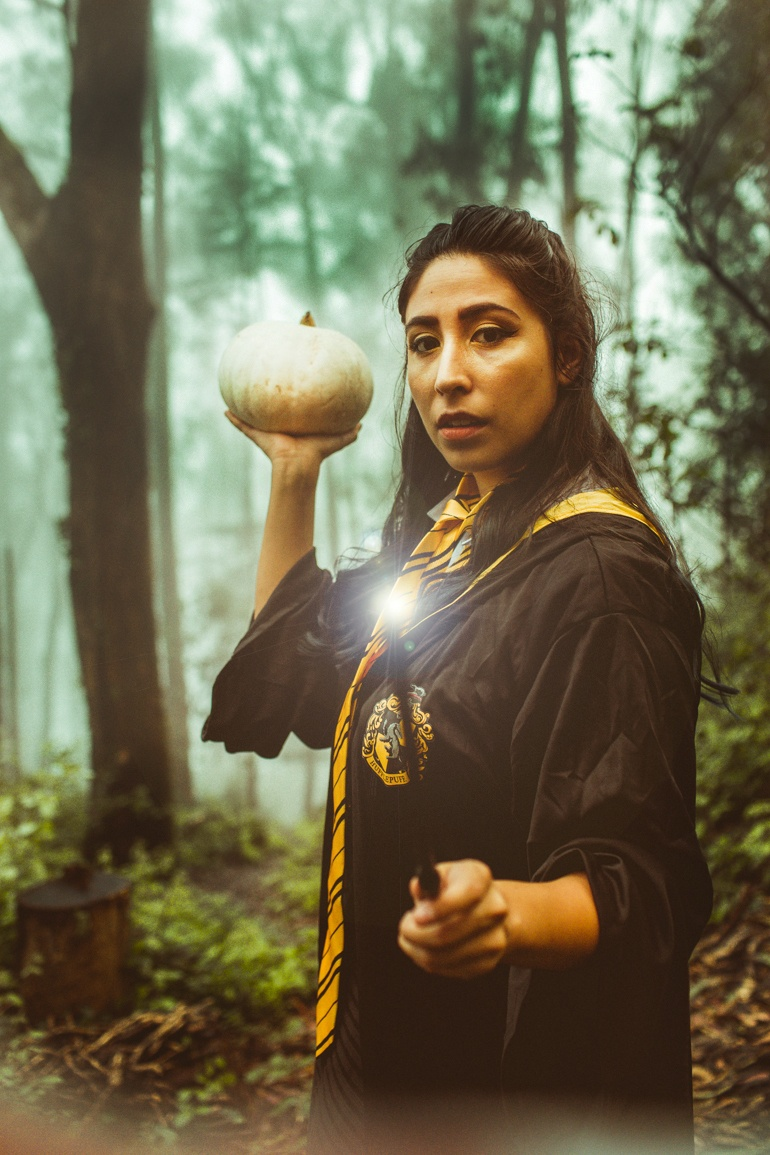 woman in Hufflepuff robe and wand