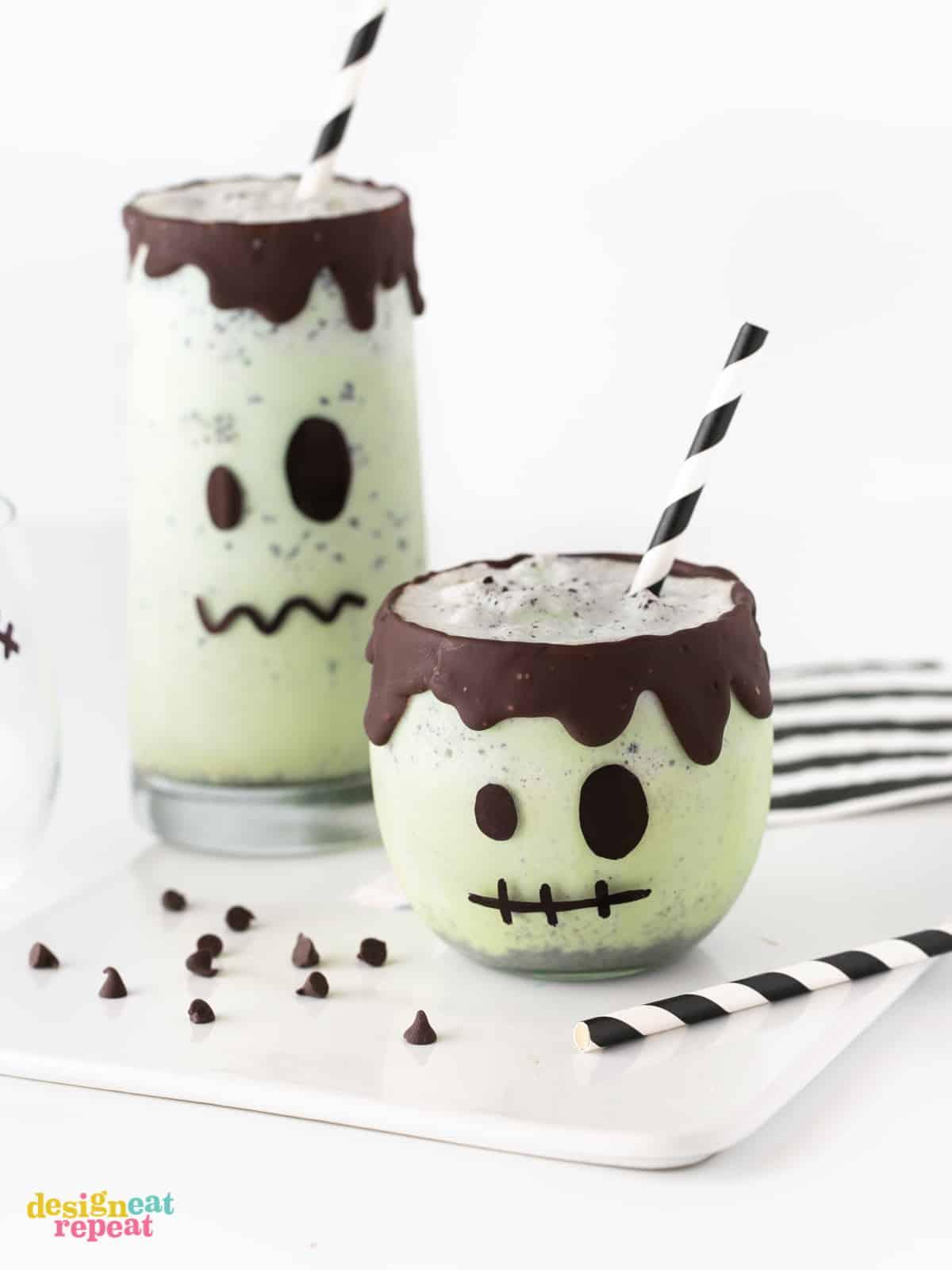 Small mint milkshake decorated like Frankenstein with chocolate rim. With paper black straw and tall Frankenstein green milkshake on white cutting board. Easy Halloween Milkshakes.