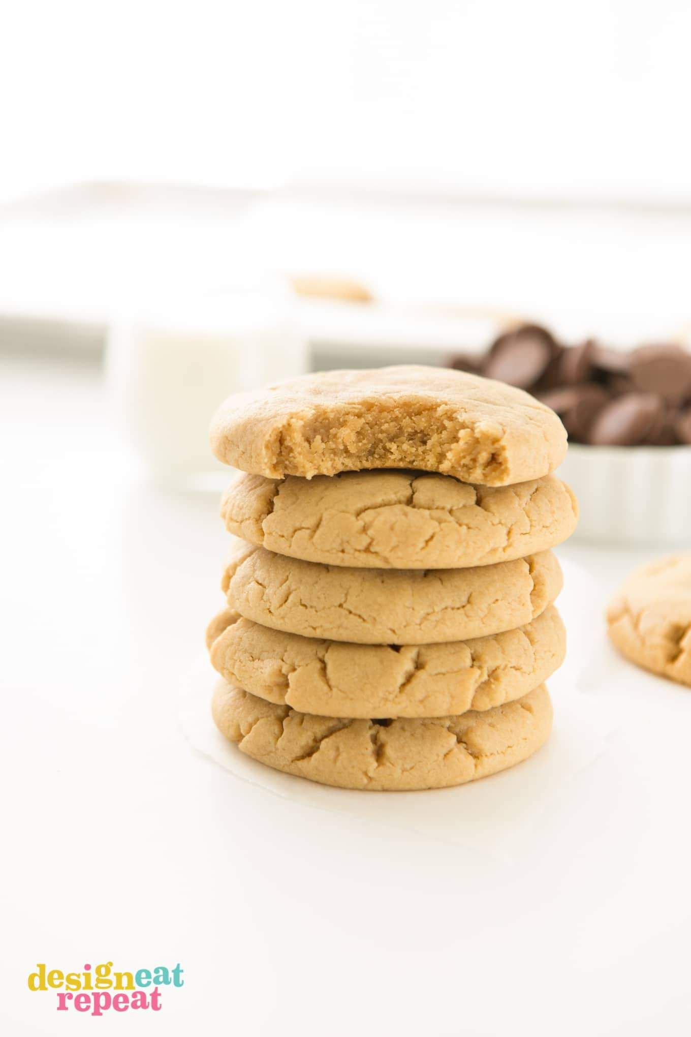 Stack of peanut butter cookies with bite taken out of top cookie.