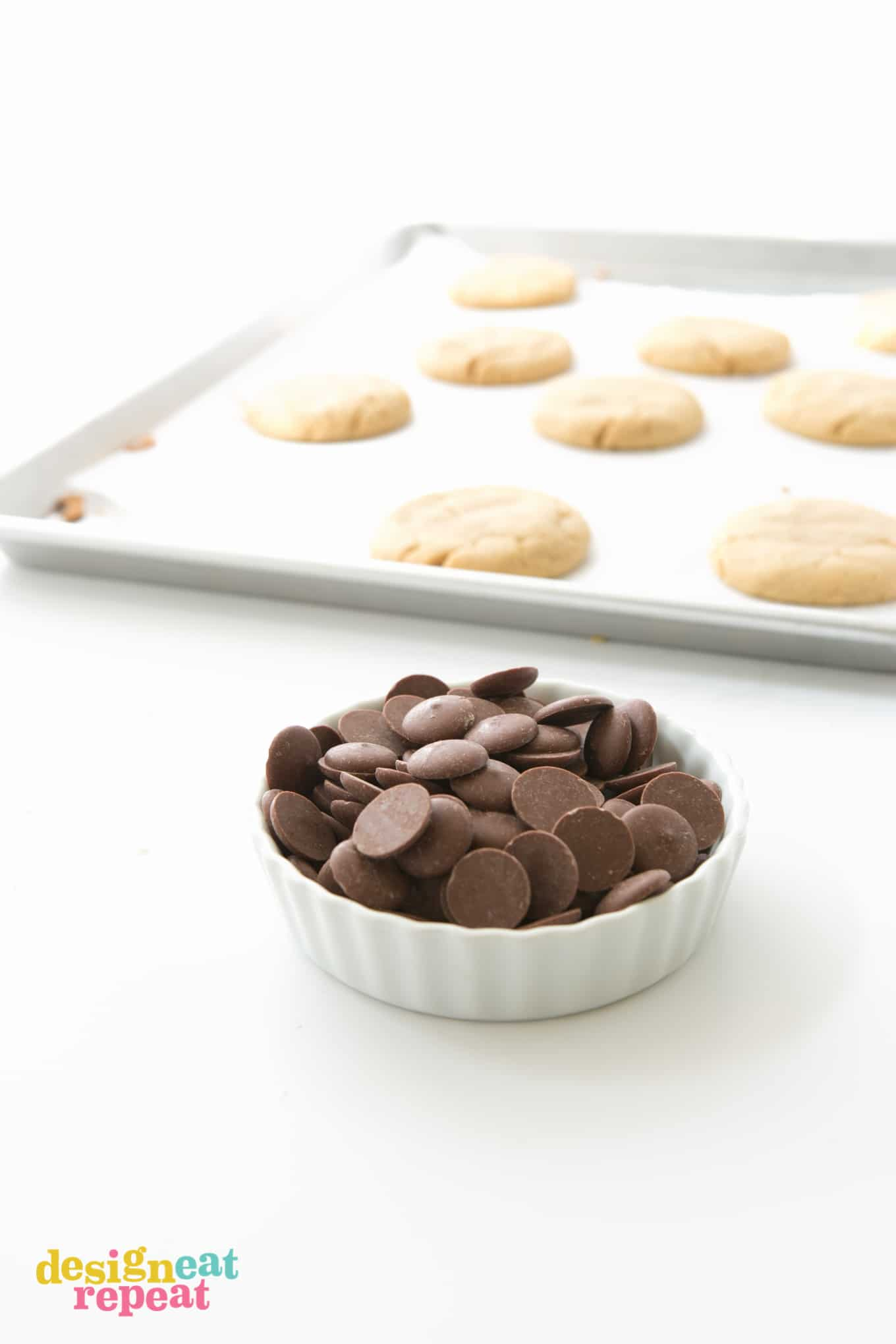 Bowl of dark chocolate melting wafers to use on peanut butter cookies.