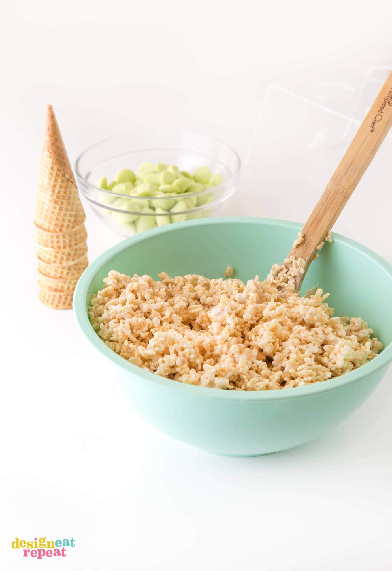 Mixing rice krispy cereal treats with wooden spoon in large blue bowl.