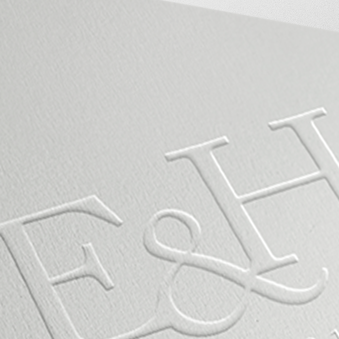 White embossed wedding monogram with two initials E ampersand H interlinked, and text est 2017 directly beneath wedding monogram