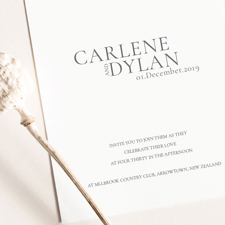 Wedding invitation with custom monogram featuring initials C D center aligned in header. At center is the couples names carlene and dylan in caps with the date directly below. In the bottom third footer placement of the card are the wedding details, time date location across four lines. All text in serif typeface capitals and center aligned