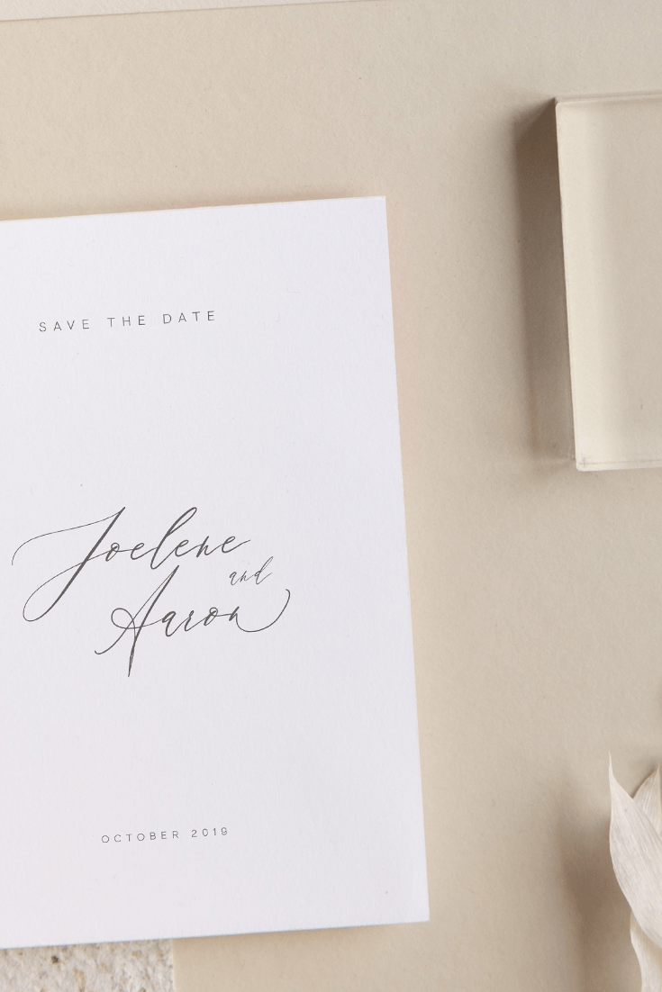 Wedding save the date card with text save the date center aligned in small caps in the header, at center is the couples names Joelene and Aaron in modern calligraphy type across three lines and center aligned with the date october 2019 in small caps center aligned in the footer