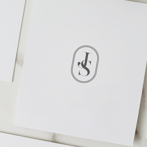 Interlinked initials J and S wedding monogram in serif type with a double line oval border