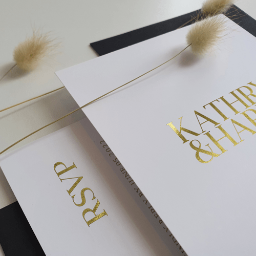 wedding invitation and rsvp in gold foil on white card in bold serif type
