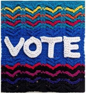 Tunisian crochet letters spell V-O-T-E against a rainbow aran crochet background.