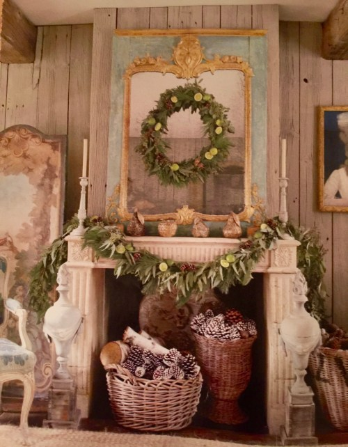 fireplace with a mirror with a wreath hanging on it